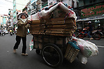 A woman pushes a large cart of recyclable material down Bui Vien Street in Ho Chi Minh City, Vietnam. Virtually everything of any value is recycled in Vietnam, and many people make a living collecting and selling cardboard, plastic bottles, paper and other items. Aug. 23, 2011.