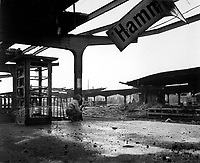 Alert for enemy movement, Pfc. Armand Rindone, Philadelphia, Pa., crouches with a carbine at the railroad station in the newly captured town of Hamm, Germany.  April 6, 1945.  T4c. Vernon M. Sharette. (Army)<br /> NARA FILE #:  111-SC-203836<br /> WAR &amp; CONFLICT BOOK #:  1093