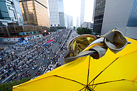 HONG KONG, HONG KONG SAR, CHINA - OCTOBER 05: An umbrella and a pair of googles, both symbolic or fighting against police's tear gas, oversee protesters on Connaught road in pro-democracy 'Occupy Central' camp in Admirality, Hong Kong, on October 5, 2014. The 'Umbrella revolution' or 'Occupy Central' is a civil disobedience movement that began in response to China's decision to allow only Beijing-vetted candidates to stand in the city's 2017 election for the top civil position of chief executive. Thousands of pro-democracy supporters are calling for open elections and the resignation of Hong Kong's Chief Executive Leung Chun-ying. (Photo by Lucas Schifres/Getty Images)