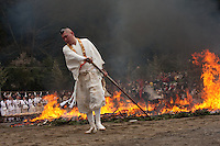 A yamabushi or mountain priest rakes out the embers of a  large bonfire of cedar branches behind him at the Hi Watari firewalking festival, Takaosan guchi near Tokyo, Japan. Sunday March 8th 2009