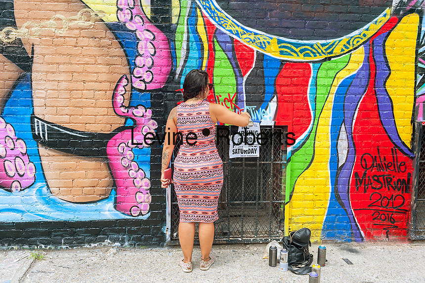 """Danielle Mastrion works on her mural in Bushwick, Brooklyn in New York during the annual Bushwick Collective Block Party on Saturday, June 4, 2016. Music and partying brought some but the real attraction was the new murals  by """"graffiti"""" artists that decorate the walls of the buildings that the collective uses.  (©Richard B. Levine)"""