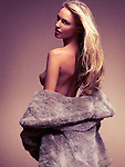 Beautiful sexy topless woman with long blond hair in fur coat over nude body