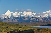 Hikers pause on a hill top near Wonder Lake to view the Alaska Mountain range, Denali National Park, Alaska.
