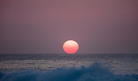A close-up of the sun in a voggy sky setting over the water at the North Shore, O'ahu