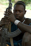 Young man with gun AK47, Mursi Tribe, Mago National Park, Lower Omo Valley, Ethiopia, portrait, person, one, tribes, tribal, indigenous, peoples, Southern, ethnic, rural, local, traditional, culture, primitive, Rifle, Weapon, Assault, Kalashnikov.Africa....