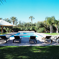 A row of sun loungers takes advantage of the shade at one end of the swimming pool