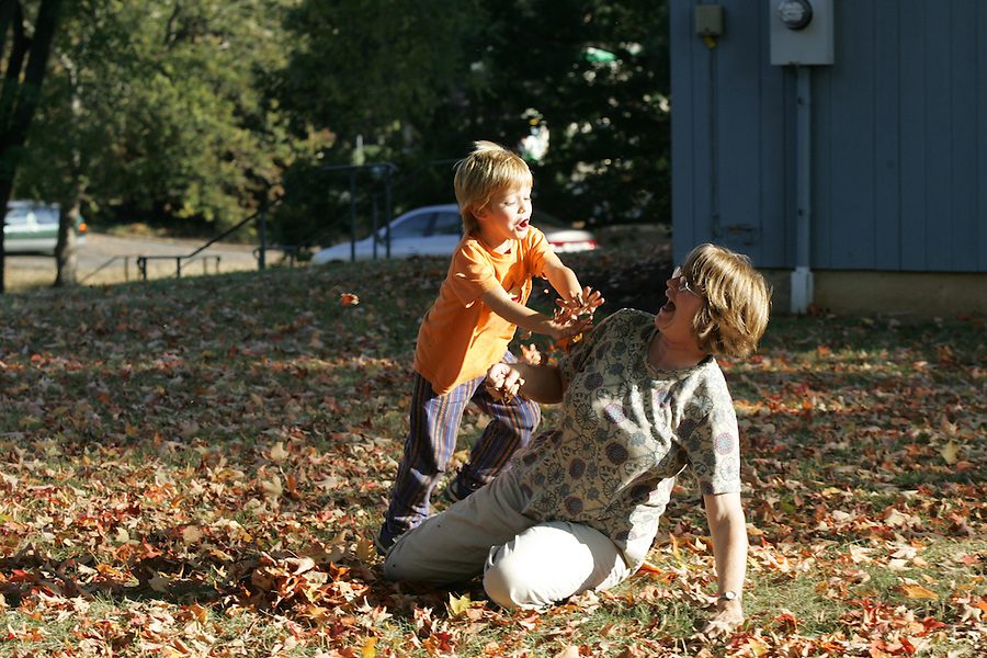 Boy playing with mother in leaves in Albemarle, VA.  Credit Image: © Andrew Shurtleff