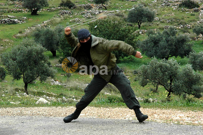 A Palestinian demonstrator hurls stones at  Israeli soldiers during a demonstration against Israel's separation barrier in the West Bank village of Bilin near Ramallah, Friday, Feb. 26, 2010.  Photo by Nedal Shtieh