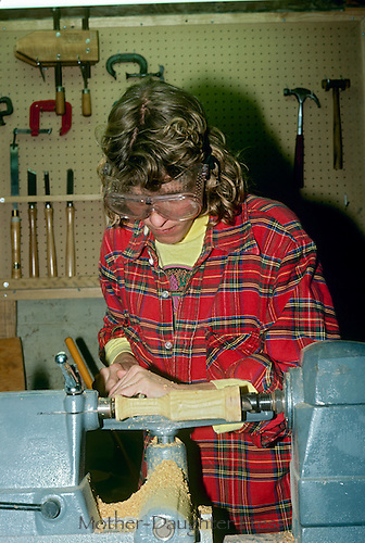 Woman woodworking in plaid flannel
