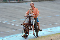 Visitors try an old wooden bicycle during a historic car race in Budapest, Hungary on September 17, 2011. ATTILA VOLGYI