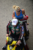 Jun. 29, 2012; Joliet, IL, USA: NHRA funny car drivers John Force and daughter Courtney Force on a scooter during qualifying for the Route 66 Nationals at Route 66 Raceway. Mandatory Credit: Mark J. Rebilas-