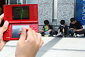 May 9, 2010 - Tokyo, Japan - Young Japanese play Nintendo's portable video game 'DS' in front of the official Pokemon store in Tokyo on May 9, 2010. Nintendo recently announced that the DS handheld device had become the best selling gaming handheld of all time, with a total of 129 million units sold. The DS 'family' have surpassed the &quot;Game Boy&quot; series which hit 118 million over two decades.