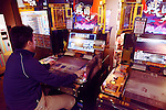 Person playing Sangokushi Taisen card game arcade slot machines in Tokyo, Japan