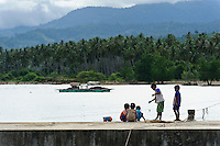 Children fishing on a jetty, Dudepo, Bolmong Selatan, Sulawesi, Indonesia.