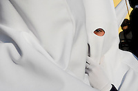 The Holy Week participants wearing a white tunic and a hood with the conical hat (capirote) walk down the street of Malaga, Spain, 5 April 2007.