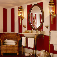 A pair of wall-mounted lanterns flank a framed oval mirror in this red and white striped bathroom