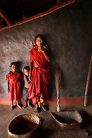 28 year old Site Wadeka, with her two children, in her home that is now lit with a solar lamp, in the tribal village of Tinginapu. She makes brooms which are sold locally. The Orissa Tribal Empowerment and Livelihoods Programme (OTELP) is an organisation funded by DFID (Department for International Development) and run with the state government of Orissa.  The project took four women from the remote tribal village of Tinginapu and trained them in Solar Powered Engineering, and installed Solar lighting in their village which had not seen electricity for over 15 years. The Orissa Tribal Women's Barefoot Solar Engineers Association has now got a contract to build 3,000 solar-powered lanterns for schools and other institutions and is training other people in the community.