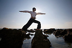 A man stretches and does yoga on a rocky beach in Koh Lanta, Thailand.