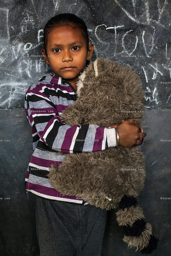 Ashia, 4, poses for a portrait with a soft toy in the Guria Non-Formal Education center in the middle of the Shivdaspur red light district, Varanasi, Uttar Pradesh, India on 20 November 2013. Guria uses the soft toys as a form of therapy for the children of the women in prostitution and also use it as signals of the children's emotional wellbeing.