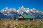 "Abandoned farm building on ""Mormon Row""  wtih the Grand Tetons Mountain Range in the background, located in the Grand Tetons National Park in Wyoming."