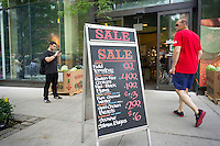 A chalkboard outside of a Whole Foods Market in the New York neighborhood of Tribeca advertises their sales on Thursday, July 31, 2014. Besieged by competitors selling essentially the same thing the company is planning a major marketing push which will include home delivery in some of its major markets (NY already has delivery services). It will also start a shopper loyalty program. In the last quarter sales had risen only 3.9 percent compared to 7.5 percent during the same period last year.  (© Richard B. Levine)