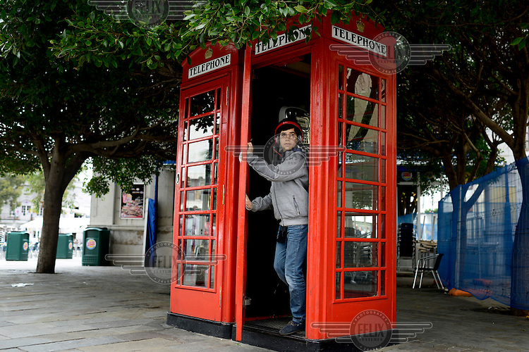 A youth leaves a traditional red British phone box.