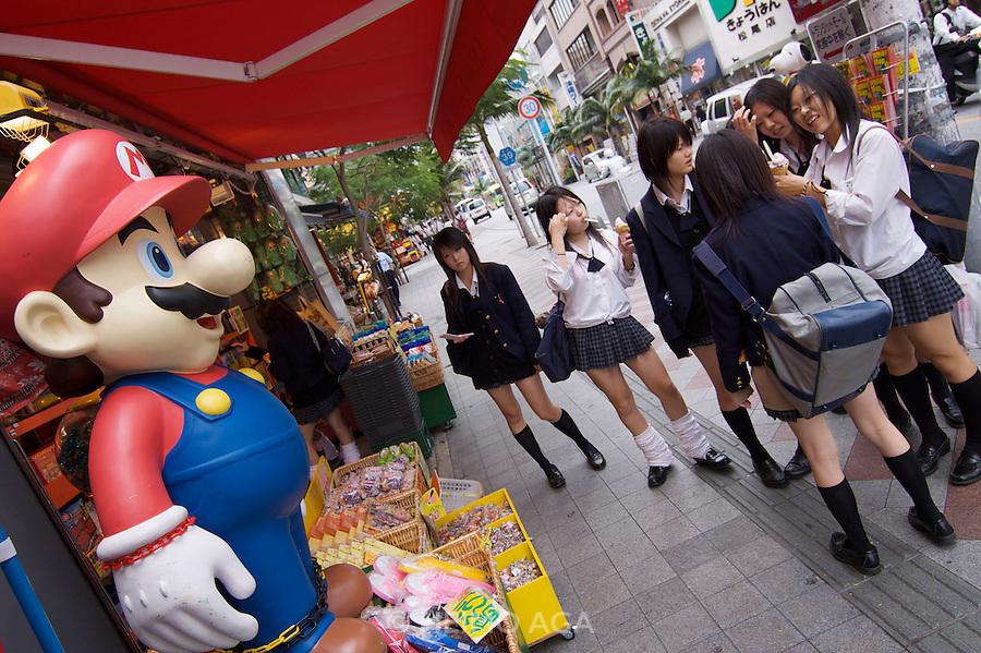 Kokusai-do?ri amusement and shopping street. School girls with Super Mario.