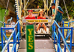 August 7, 2012 - Merrick, New York, U.S. - On Ferris Wheel bottom car, worker approaches teen girl and boy staring ahead, on the first night of the 22nd Annual Merrick Festival on Long Island. YES sign in foreground shows minium height riders must be.