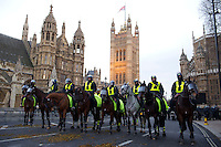 Police wear riot gear on horseback outside the Houses of Parliament on Parliament Square as they prepare to charge protestors at a student demonstration in Westminster, central London on the day the government passed a bill to increase university tuition fees.