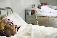 Somaliland. Waqohi Galbed province. Hargeisa. Tubeculosis (TB) hospital. Female ward. A black muslim woman, TB patient,wearing a veil on her head, lays in bed while she is taking the two months drugs as a TB treatment. White bed sheets. The Global Fund through the ngo ( non-governmental organization ) World Vision supports the programm with a Tuberculosis grant (financial aid). Somaliland is an unrecognized de facto sovereign state located in the Horn of Africa. Hargeisa is the capital of Somaliland. © 2006 Didier Ruef