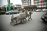 An old man labors with a cart of earth in the heart of modern Yangzhou, China, a suburb city of Shanghai and major producer of photovoltaic cells for solar power.
