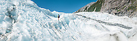 Female hiker walking over ice waves on top of terminus of Franz Josef Glacier, Westland Tai Poutini National Park, West Coast, UNESCO World Heritage Area, New Zealand, NZ