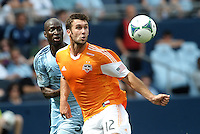 Eyes on the ball from Will Bruin (12) forward Houston Dynamo as he is watched by KC defender Ike Opara..Sporting Kansas City and Houston Dynamo played to a 1-1 tie at Sporting Park, Kansas City, Kansas.