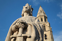 Statue of Saint Louis or King Louis IX of France, 1951, by Albert-Marius Patrisse, 1892-1964, Poissy, Yvelines, France. Behind is the Western bell tower of the Collegiale Notre-Dame de Poissy, a catholic parish church founded c. 1016 by Robert the Pious and rebuilt 1130-60 in late Romanesque and early Gothic styles. Saint Louis was born in Poissy in 1214 and baptised in this church in the same year. The Collegiate Church of Our Lady of Poissy was listed as a Historic Monument in 1840 and has been restored by Eugene Viollet-le-Duc. Picture by Manuel Cohen