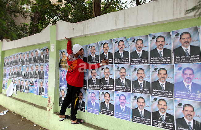 An Egyptian walks past electoral campaign posters and banners for candidates in Cairo on November 27, 2011 on the eve of the first parliament elections since the end of the 30-year rule of strongman Hosni Mubarak. Photo by Wissam Nassar
