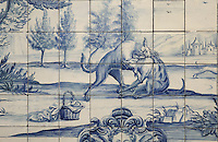 The dog with the old man's dinner round his neck, with 2 dogs fighting, from the fables of La Fontaine, traditional blue and white azulejos tile scene, 18th century, in the cloister of the Monastery of Sao Vicente de Fora, an Augustinian order monastery and church built in the 17th century in Mannerist style, Lisbon, Portugal. The monastery also contains the royal pantheon of the Braganza monarchs of Portugal. Picture by Manuel Cohen