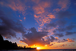 Pink clouds and silhouetted peaks at sunset over Tunnels Beach, Na Pali Coast, Island of Kauai, Hawaii USA