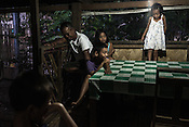 Ernesto Betasolo share a light moment with his children and grand children in the kitchen of his house in Relocation Golden Valley in Barangay Pagkakaisa outside of Puerto Princesa, Palawan in the Philippines. <br /> Photo: Sanjit Das/Panos for Greenpeace