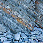 Beach abstract with blue pebbles and rock formation on beach in England