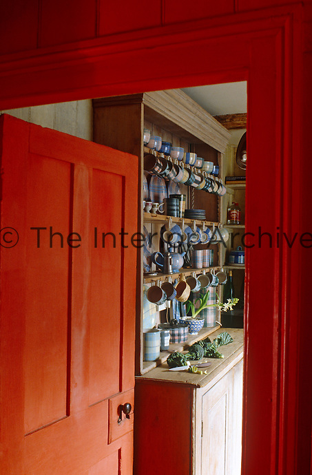 A glimpse through the open red-painted door into the kitchen reveals a dresser filled with tableware with a tartan pattern