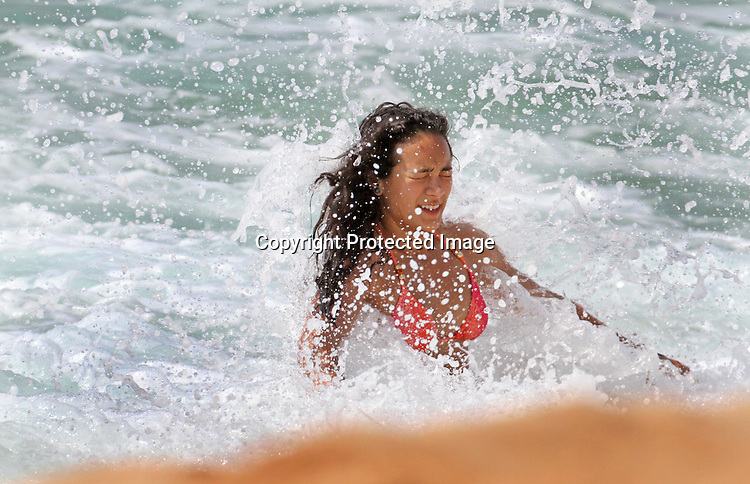 A beach goer gets a wave in her face on the shore at Ehukai Beach (Banzai Pipeline) on the Northshore of Oahu, Hawaii.