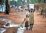 Children carry water in the Ajuong Thok Refugee Camp in South Sudan. The camp, in northern Unity State, hosts thousands of refugees from the Nuba Mountains, located across the nearby border with Sudan.