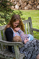 A mother  breastfeeding her child during a family outing to a local park and gardens.<br /> <br /> 11-06-2015<br /> Hampshire, England, UK<br /> <br /> &copy; Paul Carter / wdiip.co.uk