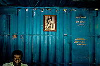 A Cuban man works in front of a portrait of the revolutionary leader Che Guevara, hung on the wall of a movable locksmithery in Alamar (the Eastern Havana), Cuba, 14 August 2008. During the Cuban Revolution, an armed rebellion at the end of the 1950s in Cuba, most of the revolutionary leaders started as no-name soldiers fighting in the jungle. Although the revolutionary leaders, after taking over the power, became autocratic rulers holding almost absolute power and putting the opposition in jail, for some reason Cuban people have never stopped to worship Fidel Castro, Che Guevara, Raul Castro and others. Cubans hang their photos and portraits on the wall in homes, shops and working places even they don't have to. The people of Cuba love their heroes.