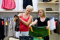 Two women comparing different clothes in shop. Retail store, fashion.