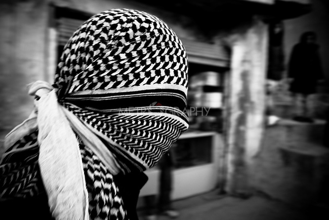 KHORRAMABAD, IRAN : A man who covers his face to remain anonymous during the festival of Ashura...Every year to mark the death of Imam Hussein, Shia Muslims mourn for two days. In Khorramabad and Lorestan in the west of Iran, during the first day of mourning, called Tasooa, women take a vow of silence and go through the streets with the children lighting candles. At 4 am on Ashura, the second day, men cover themselves in mud and then stand in front of a fire until the mud has dried to clay. After this they go to the mosque and pray...Photo by Farhad Babaei/Metrography