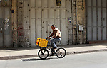 A Palestinian man rides a bicycle past closed shops during a general strike in support of Palestinian prisoners on hunger strike in Israeli jails, in the old market of the West Bank city of Nablus April 27, 2017. Photo by Ayman Ameen