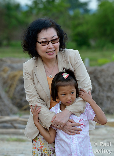 Cindy Moon, a United Methodist missionary in Thailand, comforts one of the girls living in an orphanage she founded with her husband Gary in Chiang Mai. The girls are orphans, and are all HIV positive.