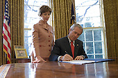 "Washington,D.C. - December, 19, 2006 -- First lady Laura Bush stands by United States President George W. Bush as he signs S. 843, the ""Combating Autism Act of 2006,"" which authorizes appropriations through FY 2011 for Autism Spectrum Disorder research, screening, intervention, and education, in the Oval Office Tuesday, December 19, 2006. .Credit: Eric Draper-White House via CNP"
