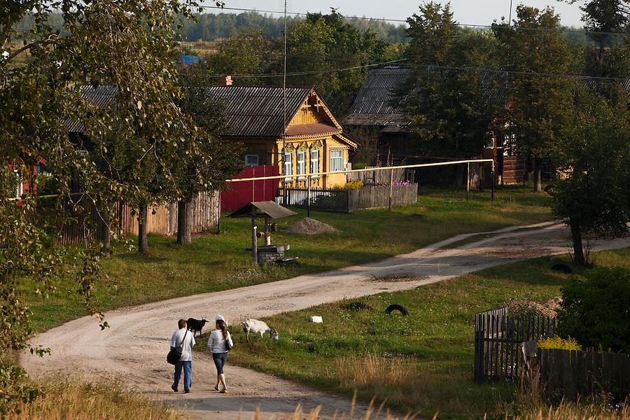 Novy Gorky, Ivanova Region, Russia, 05/08/2012..A couple walk past goats grazing in a settlement near Novy Gorky, some 200 miles east of Moscow.